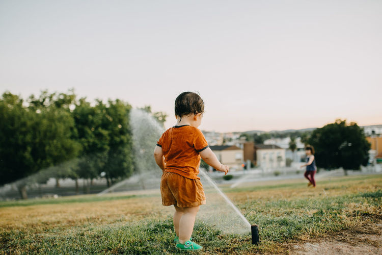 Rear view of boy playing with water sprinklers