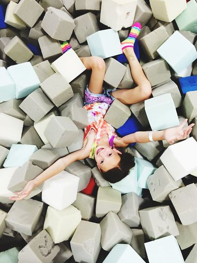 Directly above shot of girl lying while playing with sponges