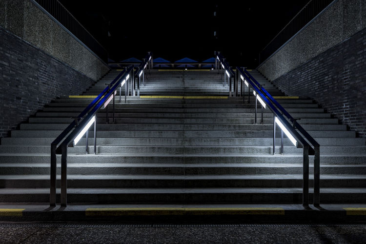 Low angle view of illuminated steps against sky at night