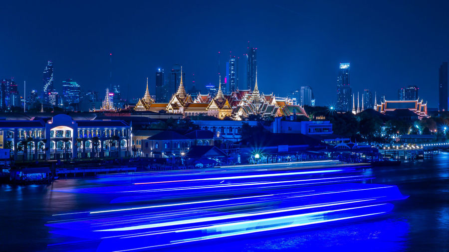 What a beautiful view of the Chao Praya River Bangkok ,Thailand. Illuminated Night Water Transportation Industry Sky Architecture Building Exterior Blue Long Exposure Nature Motion Harbor Built Structure Fuel And Power Generation Commercial Dock Pier Business Purple Chao Praya River Temple Of The Emerald Buddha Wat Phra Si Rattana Satsadaram The Grand Palace Thailand Wat Phra Kaew