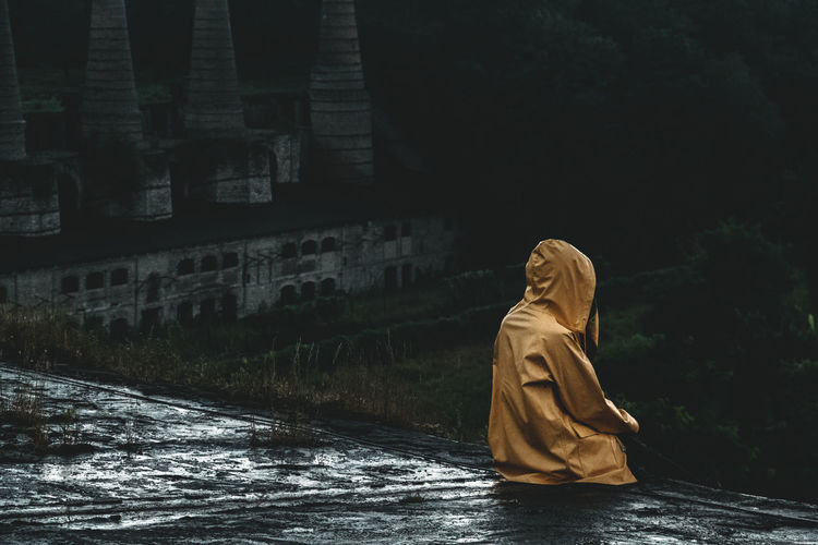 Rear view of person in raincoat sitting on rooftop