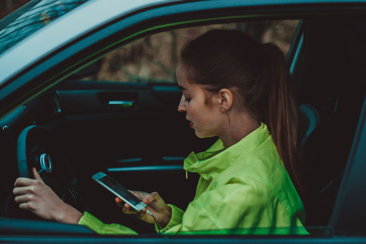 Portrait of woman using mobile phone in car
