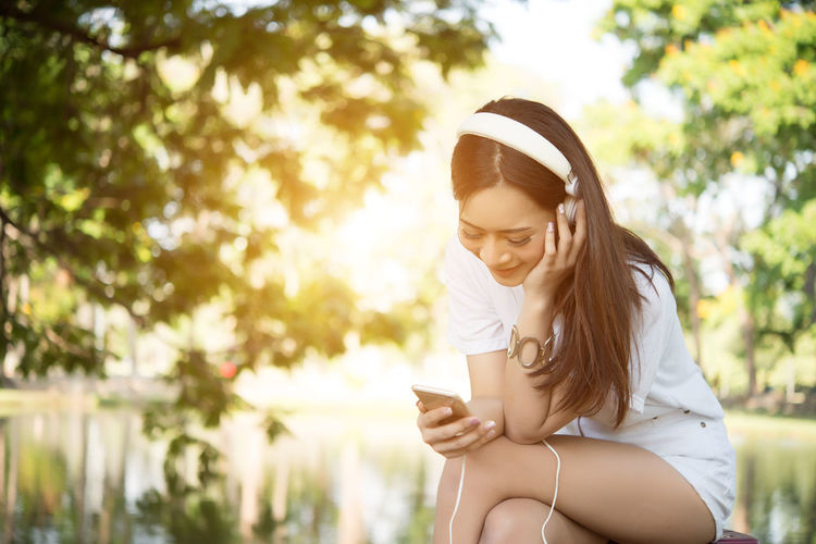 Young woman using mobile phone while sitting against lake