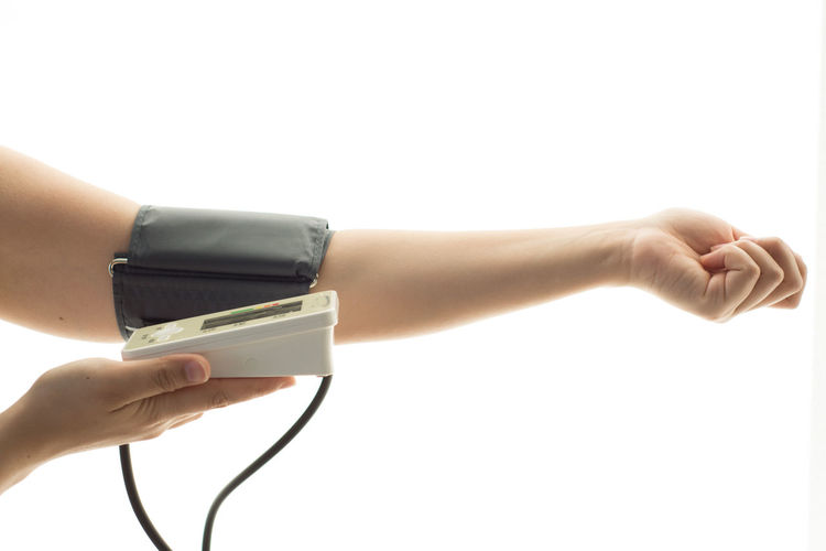 Close-up of person checking blood pressure over white background