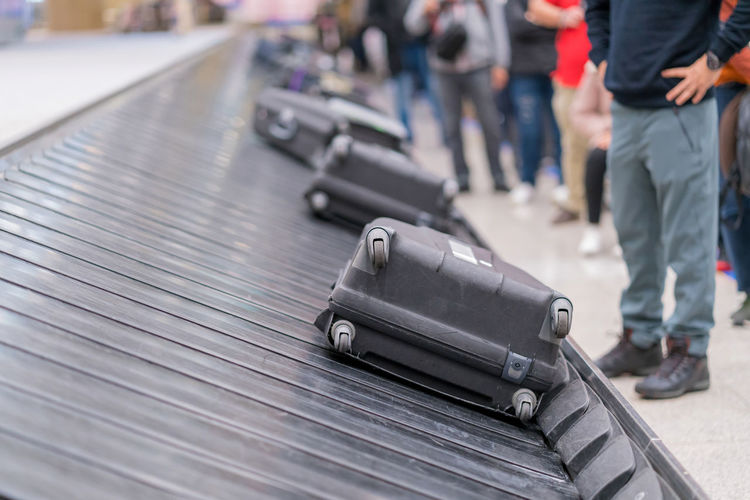 Low section of people standing by suitcases on conveyor belt at airport
