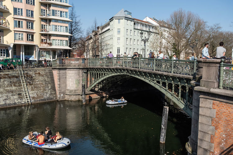 People on footbridge over canal in city