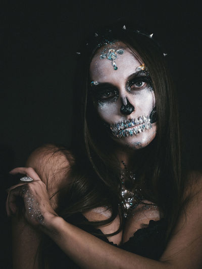 Close-Up Portrait Of Young Woman With Spooky Face Paint Against Black Background