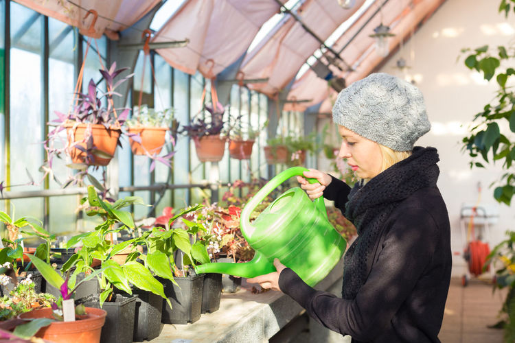 Side view of woman watering plants in greenhouse