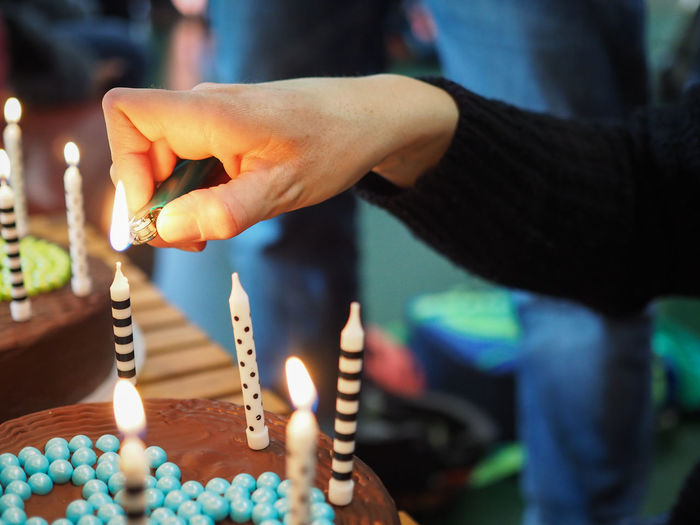 Close-Up Of Hand Lighting Candles On Cake