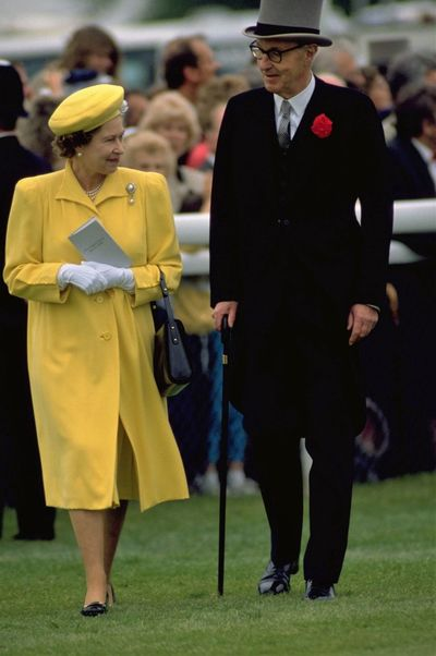Her Majesty The Queen inspects the runners and riders in the Paddock during the 1988 Derby Day race meeting. At The Races Black Shoes British Derby Day Dinner Jacket Focus Object Green Grass Her Majesty Horseracing Lifestyle London Lifestyle Long Coat People And Places People Queen Elizabeth  Royalty Top Hat Snap A Stranger Yellow