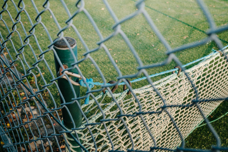 High angle view of chainlink fence on grass