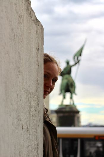 Portrait of woman standing wall against statue