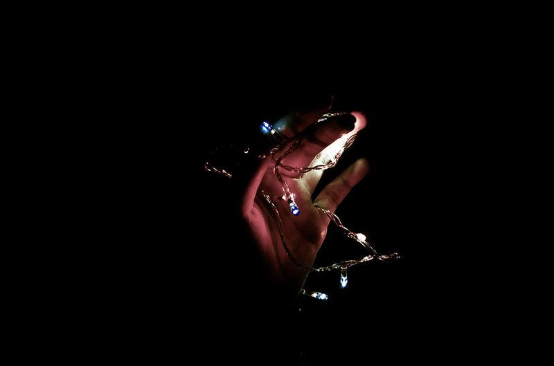 Midsection of man holding illuminated lighting equipment at night