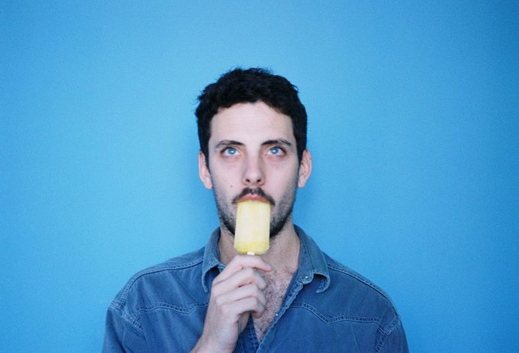 Portrait of young man eating food against blue background