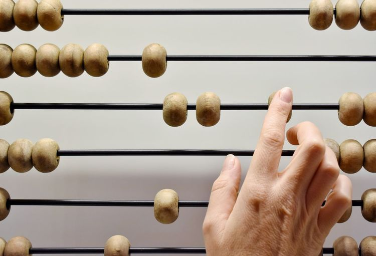 Cropped hand touching abacus