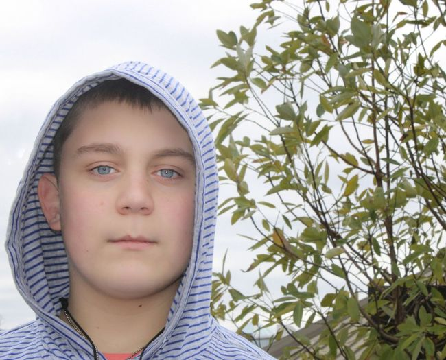 13 yr old boy with hooded shirt beautiful blue eyes the thinker outdoors trees