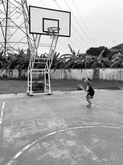 Boy playing with basketball on sports court