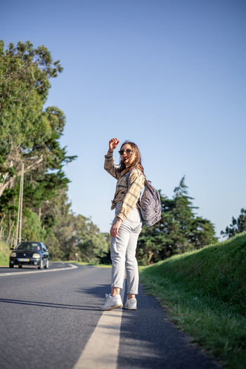 Full length of young woman standing on road against sky