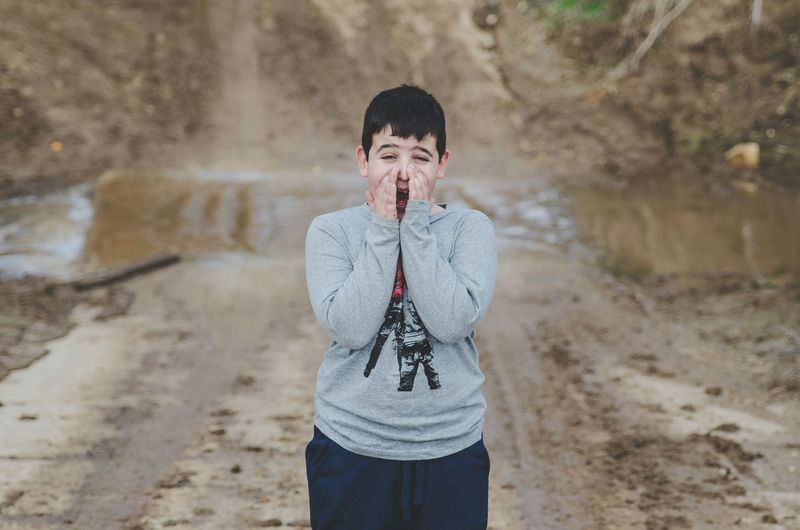 Boy shouting while standing on muddy field