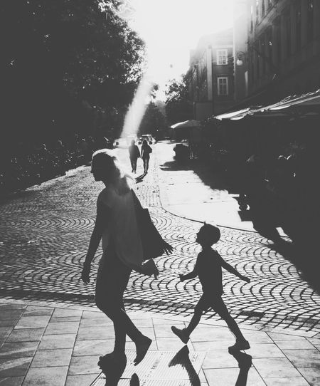 Rear view of father and daughter walking on street