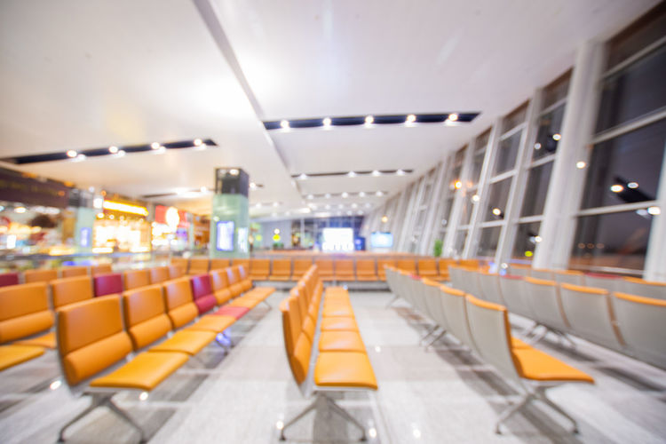 Illuminated Indoors  Absence Ceiling Empty Lighting Equipment In A Row Seat No People Architecture Transportation Flooring Public Transportation Built Structure Airport Modern Chair Electric Light Orange Color