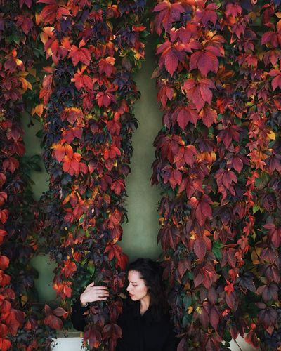 Young Woman Holding Ivy Against Wall