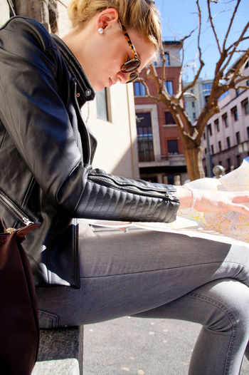 Side view of young woman looking in map while sitting at street during sunny day