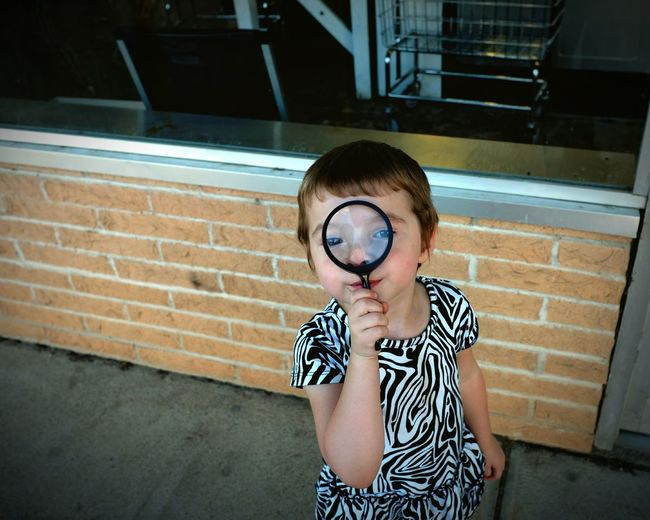 Portrait of cute girl looking through magnifying glass on sidewalk