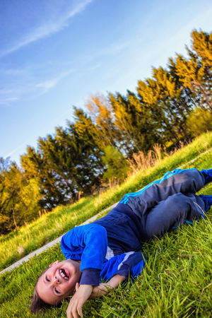 A boy can't stop laughing. Boy Laughing Casual Clothing Cheerful Enjoying The Moment Enjoying The Nature Enjoyment Flattening Grass Green Color Happiness Happy Boy Happy Time Joyfull Moment Kid Portrait Laughing Lying Down Nature Relaxation Scrambled Sunrise Colors Wood