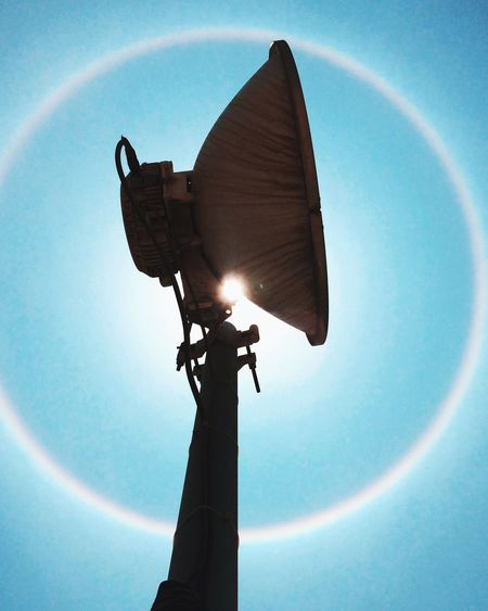 Spotlight against halo in blue sky