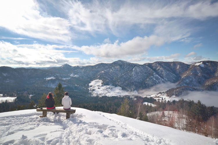 Man And Woman Sitting On Snow Covered Field By Mountains Against Sky