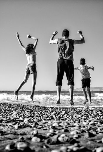 Rear view full length of father jumping with children on shore at beach