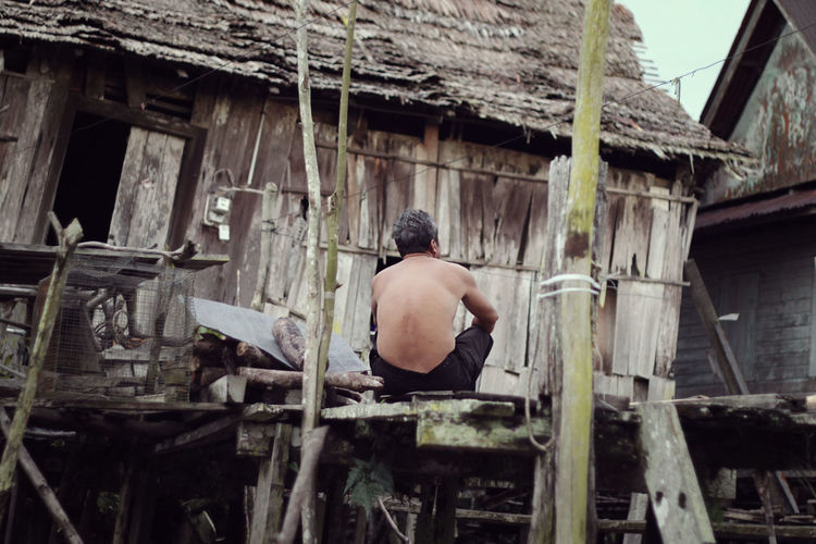 Rear view of shirtless man sitting on boardwalk by hut
