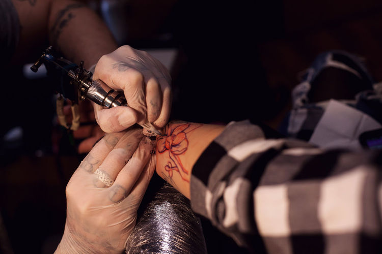 Close-up of tattoo artist making tattoo on hand of client