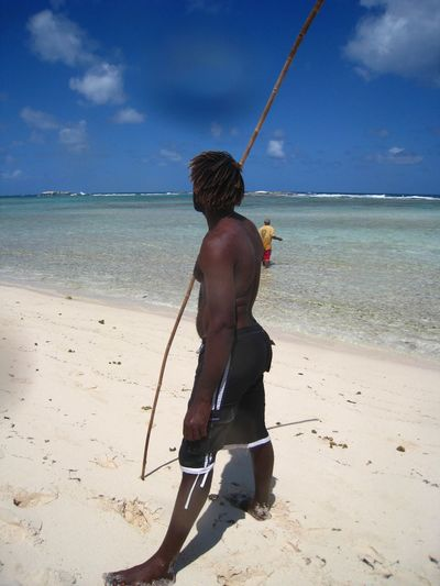 Man in tribal clothing standing on beach