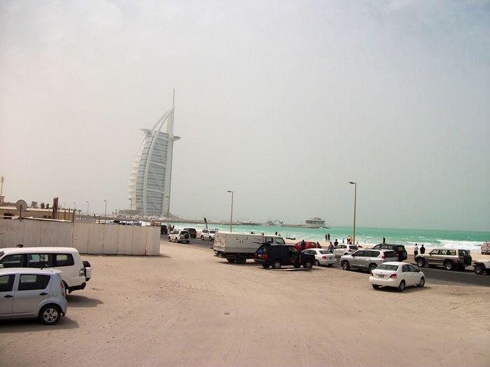 Cars on beach against sky in city