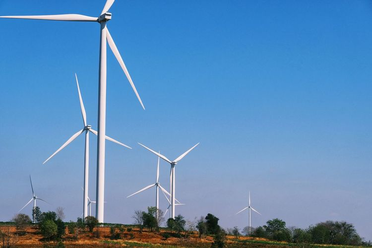 Wind turbines on landscape against clear blue sky