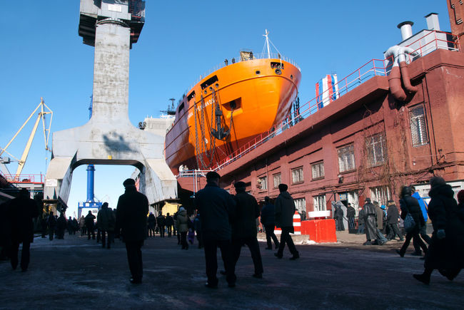 """The launch of the research vessel """"Akademik Tryoshnikov"""" at the St.Petersburg Admiralty Shipyard, March 29, 2011 Blue Construction Crane Launch Of The Vessel Orange Color Outdoors People Research Vesse S Ship Construction Shipyard Shipyard Crane Shipyardlife Sky Snow Sunny Vessel Winter"""