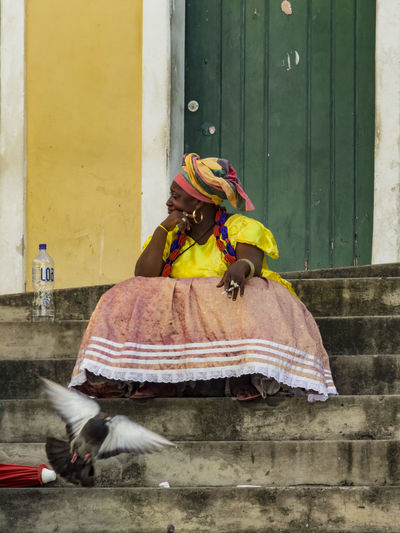 middle age brazilian women dressed in traditional clothes, sitting smoking outside on stairs ignoring the enviroment Salvador Bahia Brasilia Women Day Hair Turban Lifestyles One Person Outdoors Pigeon Real People Sitting Outdoor Smoking Cigarettes. Traditional Dress