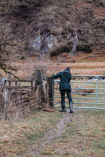 opening a farm gate Gate Opening Wales UK Young Female Young Woman Winter Countryside Rural Scene British Metal Gate Metal February Working Manual Worker Full Length Standing Occupation Agriculture Field Worker Female Alone Agricultural Field Farmland