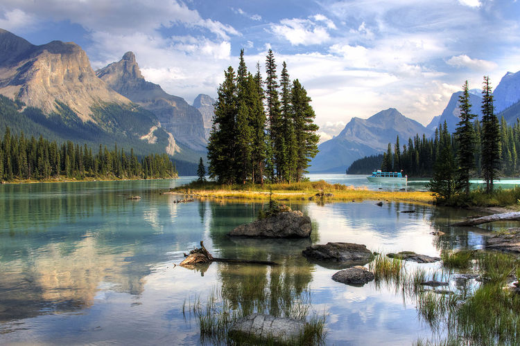 Scenic view of lake by mountains against sky in forest