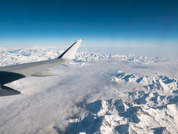 Aerial view of the Italian Swiss Alps in winter, with generic aeroplane wing. Snowcapped mountain range and glaciers. Expansive view, clear blue sky. Keywords: aerial,alps,view,wing,aircraft,jet,italy,switzerland,south america,andes,peru,bolivia,argentina,expansive,chile,above,flying,flight,mountain peak,transportation,rocky mountains,blue,engine,stunning,glacier,italian,france,swiss,extreme terrain,mountain range,airplane,beautiful,nature,airline,landscape,plane,travel,mountain,vacation,scenic,remote,valley,beauty,sky,scenics,national park,majestic,idyllic,nobody Aerial View Air Vehicle Aircraft Wing Airplane Airplane Wing Beauty In Nature Blue Clear Sky Cold Temperature Day Flying Journey Landscape Mid-air Mode Of Transport Nature No People Outdoors Scenics Sky Snow Space Transportation Travel Winter