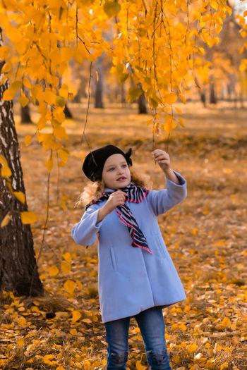 Full length of girl standing on field in park during autumn