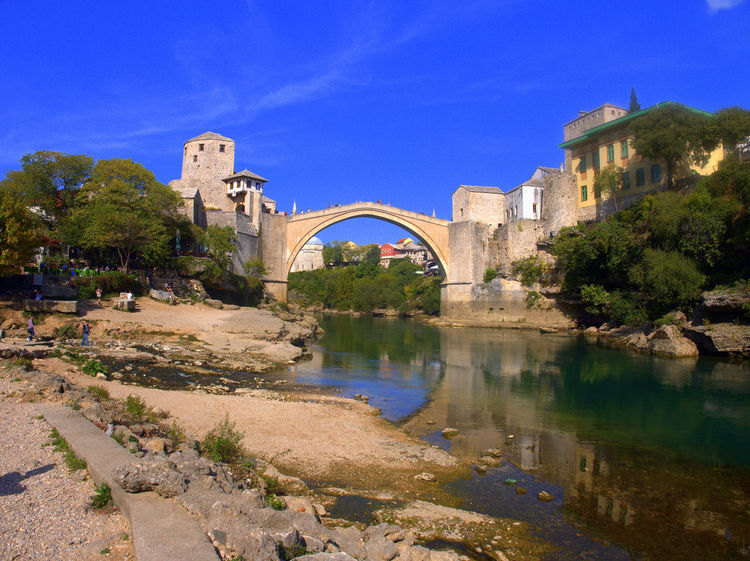 View of the bridge in Mostar from a beach Bosnia And Herzegovina Mostar Mostar Bosnia Mostar Bridge Arch Arch Bridge Architecture Bosnia Bridge Bridge - Man Made Structure Building Exterior Built Structure Connection Day Nature No People Outdoors Reflection Sky Tree Water