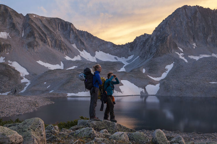 Men standing on mountain by lake against sky