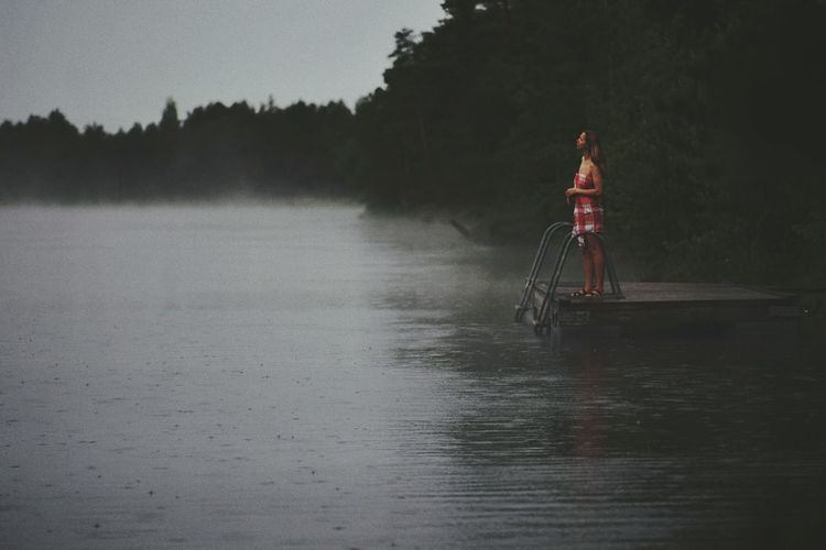Woman Standing On Pier In Lake Against Sky