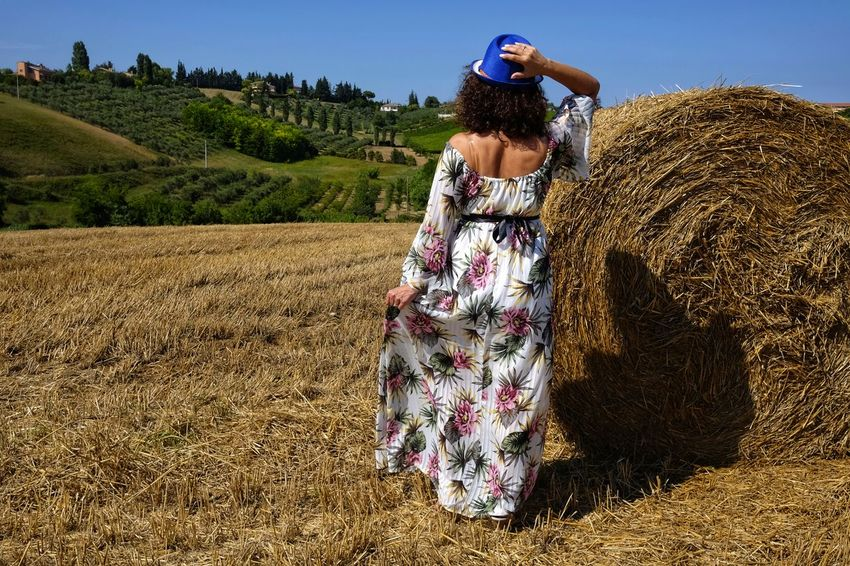 beautiful woman between round bales From Behind Hat Woman Adult Agriculture Bale  Beauty Crop  Day Environment Field Grass Harvesting Hay Land Landscape Nature One Person Outdoors Plant Rear View Rural Scene Sky