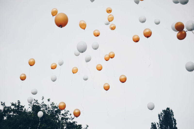 Low angle view of gold and white balloons against sky