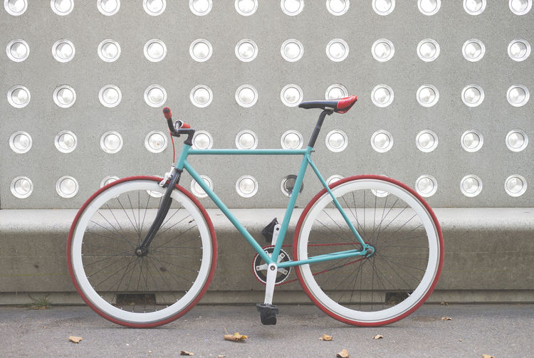 Bicycle parked on wall by street