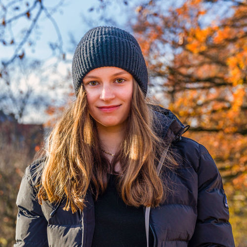 Portrait of smiling young woman in park during autumn